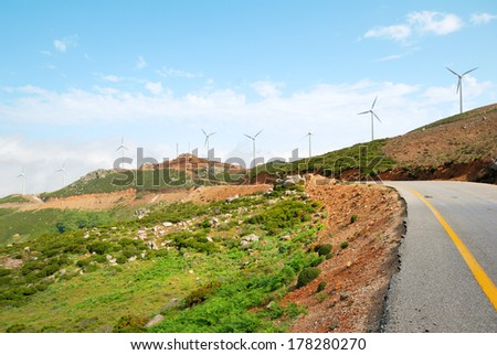 Multiple wind turbine power plants and a lonely road - stock photo
