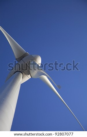 Multiple Wind turbines producing alternative energy with a blue sky - stock photo