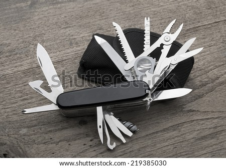 multipurpose pocket knife on wood - stock photo
