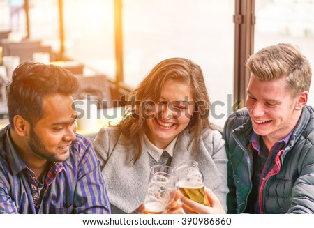 Multiracial best friends drinking a beer together sitting in bar - Happy people having fun together - Interracial friendship concept - Warm filter with artificial sunlight - Soft focus on girl's face