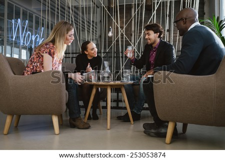 Multiracial business team sitting in office lobby discussing new business ideas. Young man drinking water. Happy young people during meeting. - stock photo