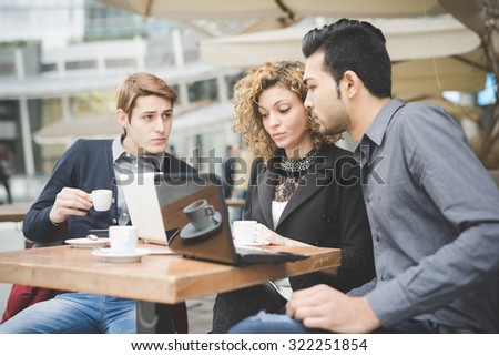 Multiracial contemporary business people working connected with laptop, talking together, looking the screen, drinking coffee - finance, business, technology concept - stock photo