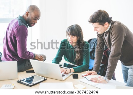 Multiracial contemporary business people working connected with technological devices like tablet and laptop, talking together - finance, business, technology concept - stock photo