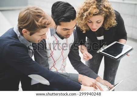 Multiracial contemporary business people working outdoor in town connected with technological devices like tablet and laptop, looking down the screen - finance, business, technology concept - stock photo