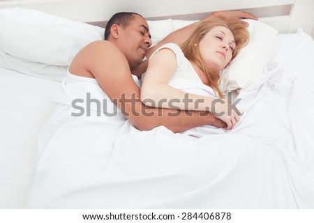 Multiracial couple hugging and sleeping
