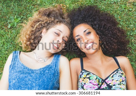 Multiracial couple lying on the grass. They are two young women resting at park. One is caucasian and the other is black, both have curly hair. They are smiling and wearing summer clothes. - stock photo