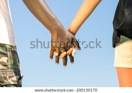 Multiracial couple walking hand in hand against a blue sky - Concept of multi ethnic love over social barriers - stock photo