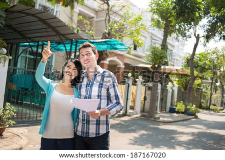 Multiracial couple watching at the house - stock photo
