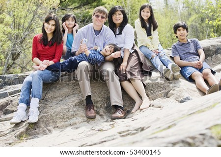 Multiracial Family sitting together on rocky ledge