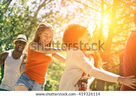 Multiracial friends dancing in garden party during summer time - Cheerful young people having fun outdoor - Multi ethnic friendship concept - Focus on blond girl - Vintage editing - stock photo