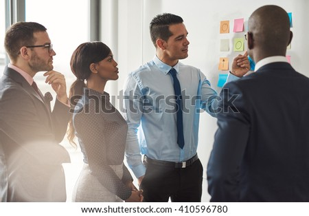 Multiracial group of businesspeople standing discussing colorful memos on a wall in a concept of teamwork and cooperation - stock photo