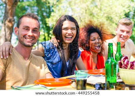 Multiracial group of friends eating and enjoying barbecue summer meal party - Young people having fun in park outdoor - Happiness with food concept - Vivid cross processed filter - stock photo