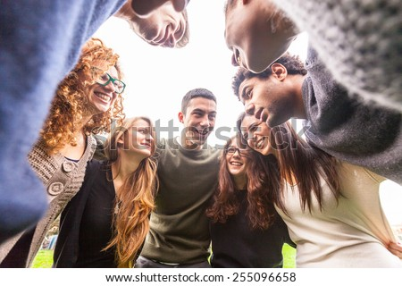Multiracial group of friends embraced in a circle, strong concept about teamwork and cooperation, also refers to immigration and friendship. - stock photo