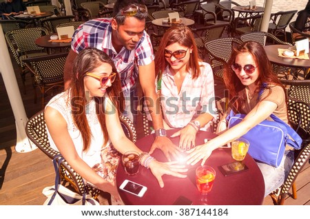 Multiracial group of friends hands circle on table with phones and drinks - Sun glow ball on hands as concept of friendship power between different cultures peoples - Main focus girl on the middle