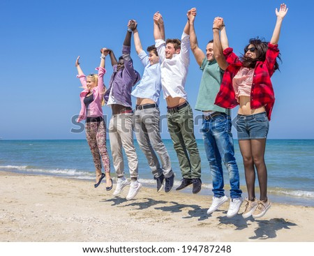Multiracial group of friends jumping on the beach - stock photo