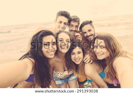 Multiracial group of friends taking selfie on the beach, camera point of view. They are teenagers, four girls and three boys, standing just next to the seaside. - stock photo