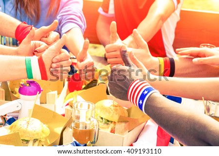 Multiracial group of friends thumbs up wear world flags cuffs - International sport fans hands circle and fun moment eating in cafe bar restaurant - Friendship joy peace concept - Focus on black hand - stock photo