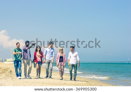 Multiracial group of friends walking on the beach - Several people of diverse ethnics talking and having fun on summer vacation - stock photo