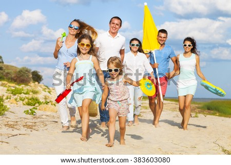 Multiracial group of friends with children running at the beach