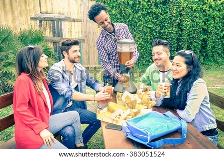 Multiracial group of happy friends eating and toasting at garden barbecue party - Concept of happiness with young people outdoors enjoying picnic food together - Vintage filtered look - stock photo