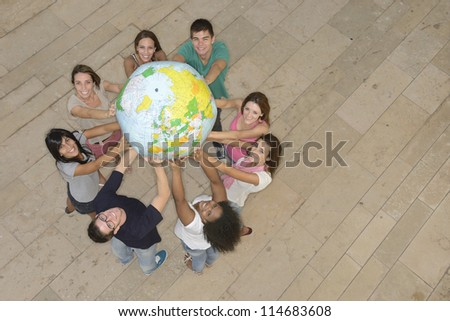 Multiracial group of people holding  the Earth Globe showing Europe - stock photo