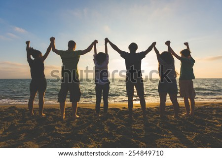 Multiracial group of people with raised arms looking at sunset. Backlight shot. Happiness, success, friendship and community concepts. - stock photo