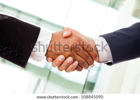 Multiracial handshake from an african and a caucasian businessman at the office - stock photo