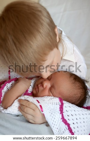 Multiracial happy family. White brother hugging black newborn sister. - stock photo