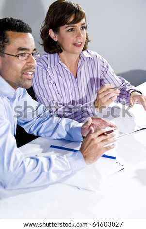 Multiracial office workers in boardroom meeting watching presentation, taking notes, focus on woman