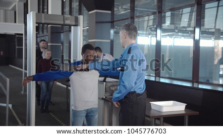 Multiracial people in airport going through gates having security control with guards.
