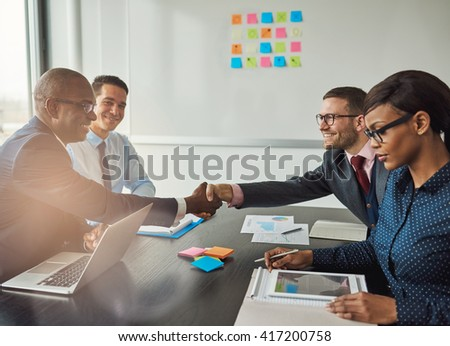 Multiracial team concluding a business agreement reaching across the table to shake hands with pleased smiles with focus to a young African woman in the foreground reading a tablet-pc - stock photo