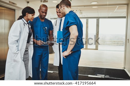 Multiracial team of doctors discussing a patient looking at tablet, surgeons and medical doctors - stock photo