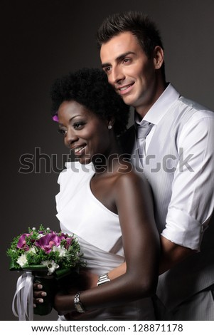 Multiracial wedding couple posing in a studio - stock photo