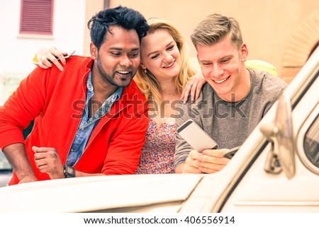 Multiracial young friends watching mobile phone on car bonnet - Cheerful guys leaning on vintage auto using smartphone technology - Concept of multicultural friendship and joyful moment on a road trip - stock photo