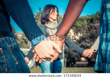Multiracial Young People Holding Hands in a Circle - stock photo