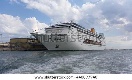 Multistory white passenger ocean ship parked in the dock - stock photo
