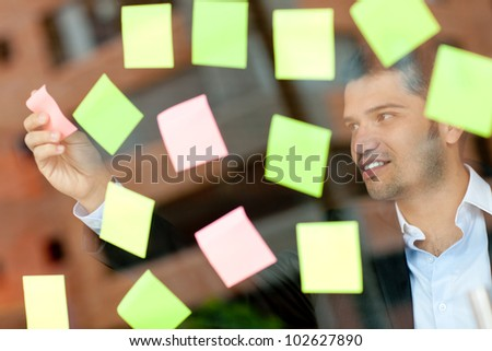 Multitask business man with lots of post-its - stock photo