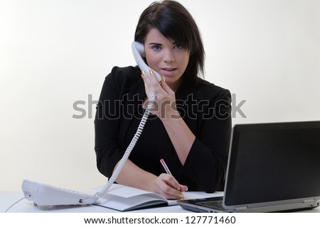 multitasking woman sitting at her desk trying to get through the day - stock photo