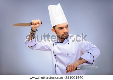 Multy tasking is a chefs game.  Closeup portrait of young handsome cook in uniform and hat gesturing with a big culinary knife and shouting while standing over grey background with copy space - stock photo