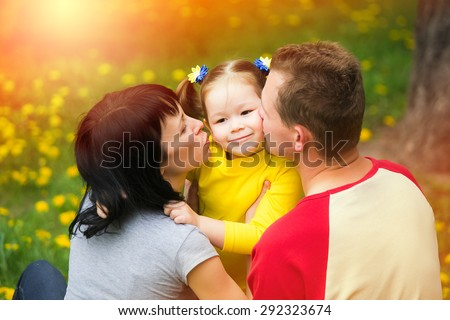 Mum and dad kissing cheeks of daughter. Happy family concept. Portrait of beautiful kid playing outside with parents.Young family spending time outdoor on a summer day.  - stock photo