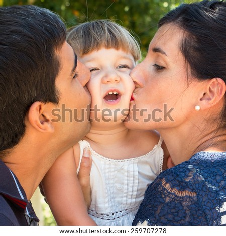 Mum and dad kissing tight baby face outdoors in a warm day