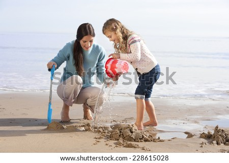 Mum and Daughter Building Sandcastles - stock photo