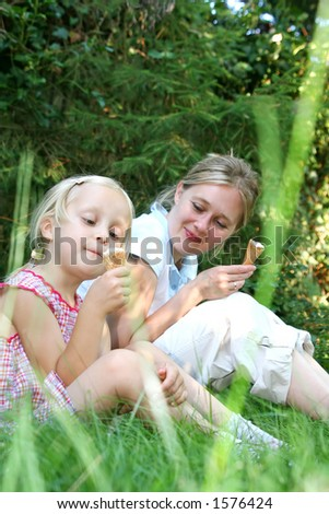 Mum and daughter in the park, focus on little girl. - stock photo