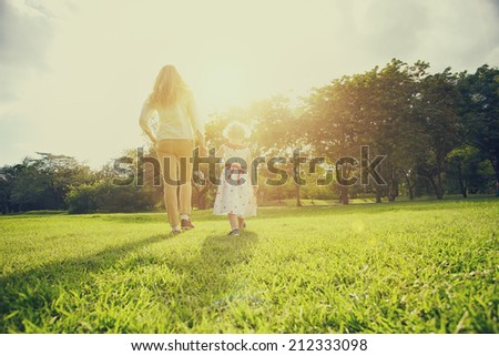 Mum and daughter outside in the park - stock photo