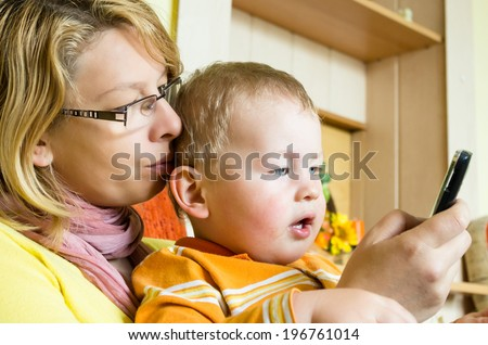 Mum and her small son read sms - stock photo