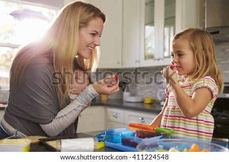 Mum and older daughter eating fruit, while baby sleeps in baby carrier - stock photo