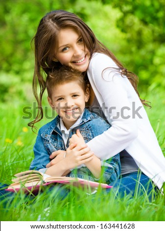 Mum and son with book sitting on green grass in green park. Concept of happy family relations and carefree leisure time - stock photo