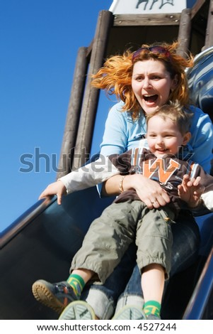 Mum and the son go for a drive on an attraction - stock photo