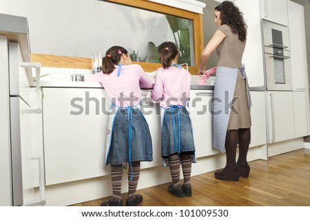 Mum and twin daughters washing up dishes in a home kitchen. - stock photo