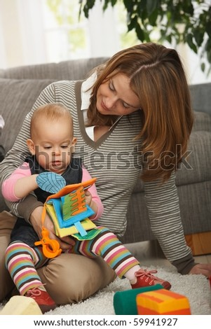 Mum holding baby daughter playing together with toys on living room floor.?